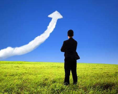 성장: 비즈니스 사람이 현장에 서서 성장 그래프 구름을보고
