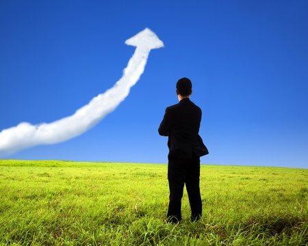 business man stand on the field and watch growth graph cloud photo