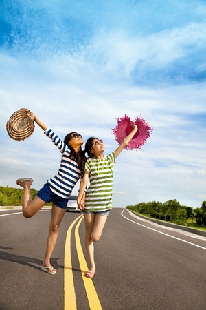 adventure holiday: two girls having fun on the road trip at summertime