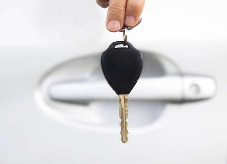 손으로 자동차의 문 전에 자동차 키를 들고