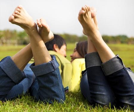 pies masculinos: feliz pareja tumbada en la hierba Foto de archivo