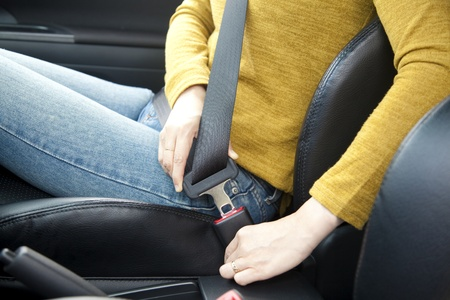 seat belt: woman hand fastening a seat belt in the car Stock Photo