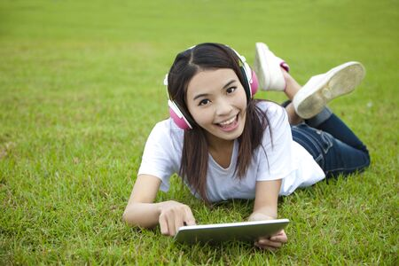 young woman using tablet pc on the grass  Stock Photo
