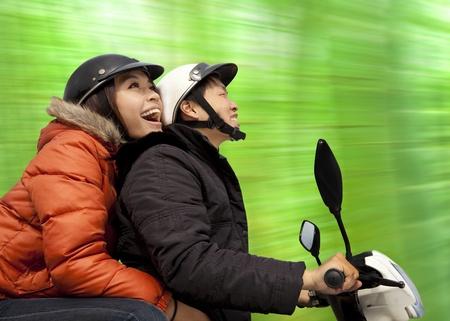 vespa: feliz pareja montando en la bicicleta en el momento de la primavera
