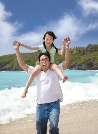 Happy girl and father on the beach photo