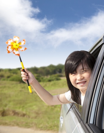 happy little girl holding windmill in the car photo