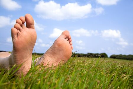 bare feet: relaxed foot on grass with cloud background