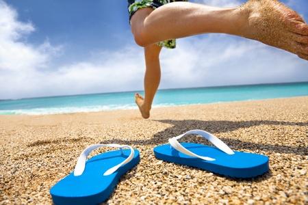 sandalia: hombre corriendo en la playa y zapatillas Foto de archivo