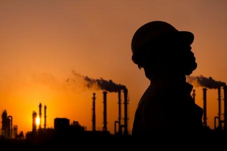 refiner�a de petr�leo: la silueta de trabajador de la refiner�a de petr�leo en el ocaso Foto de archivo
