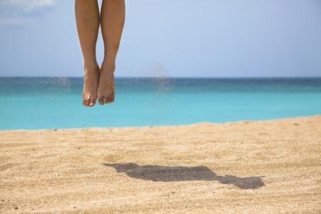 feet in sand: Man jumping on the beach