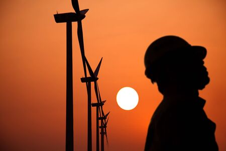 harmless: The Silhouette of windmills worker with  sunset