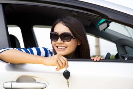 auto leasing: young woman holding key in car Stock Photo