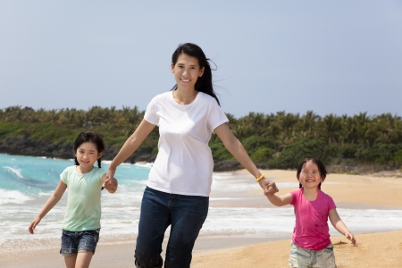 asian mother with children walking on the beach photo