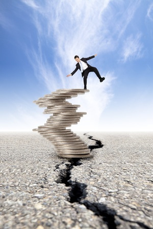 unstable: busines and Economic crisis concept  cracked road and unstable businessman on the money tower Stock Photo