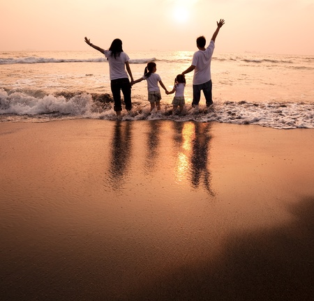 happy family  holding hands on beach and watching the sunset photo
