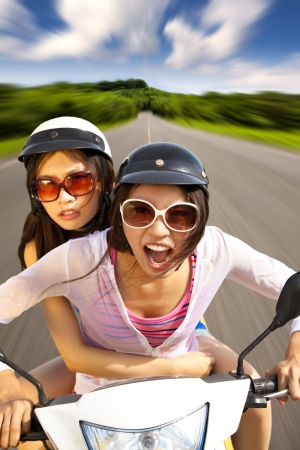 free riding: two girls riding scooter on the road Stock Photo