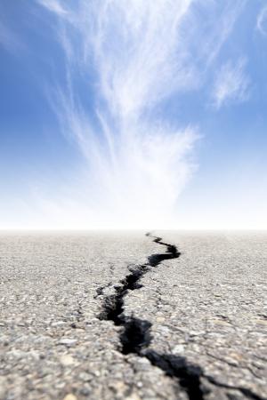 землетрясение: трещины дороге с облаками фоне