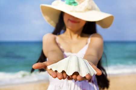 smiling young woman holding shell on the beach Stock Photo - 13295694