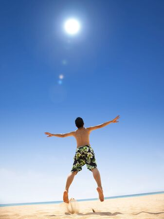 happy young man jumping on the beach Stock Photo - 13321250