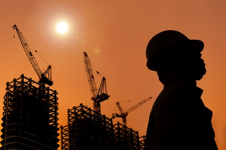The Silhouette of Construction workers with sunset photo