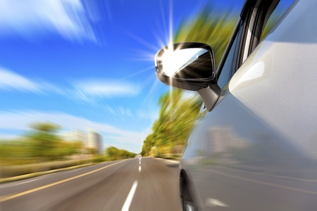 car on the road with motion blur and sunlight in the mirror Stock Photo