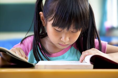 little girl studying in classroom at school photo