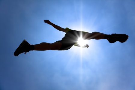 across: The Silhouette of runner acrossing sky with sunlight background Stock Photo