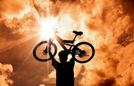 winning race: The Silhouette of mountain biker raised bicycle with sunset and cloud background