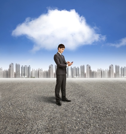 businessman holding smart phone with cloud computing background photo