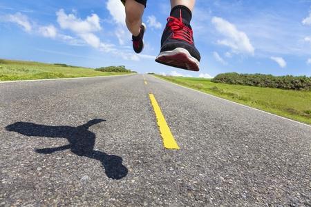 hombre deportista: las piernas y los zapatos de corredor en acci�n en la carretera Foto de archivo