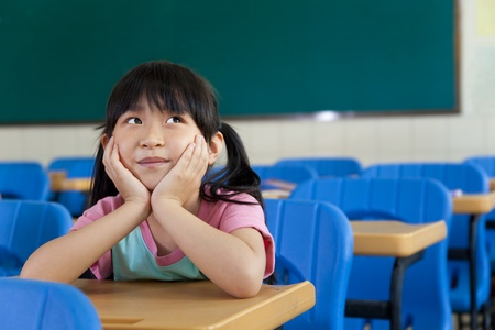 Little Girl are Thinking in the classroom of school photo