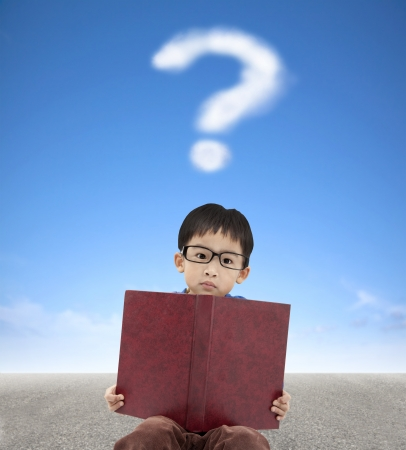 queries: little boy holding book and question mark cloud background Stock Photo