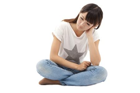 menstruacion: joven mujer triste y depresión aislada en blanco Foto de archivo
