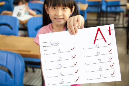 exam results: smiling little girl showing exam paper with a plus in the classroom