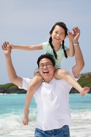 father daughter: asian father with little girl running on the beach Stock Photo