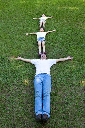 happy family lying on the grass photo