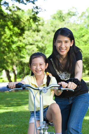 asian mother Teaching daughter To Ride A bicycle photo