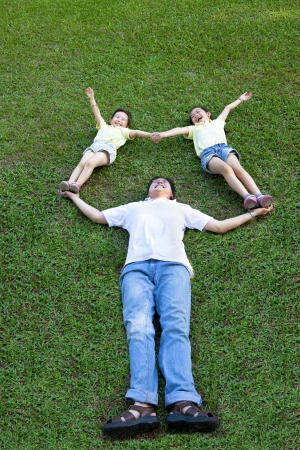 happy asian family lying and playing on the grass photo