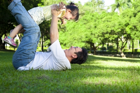 happy asian family: happy father and little girl on the grass