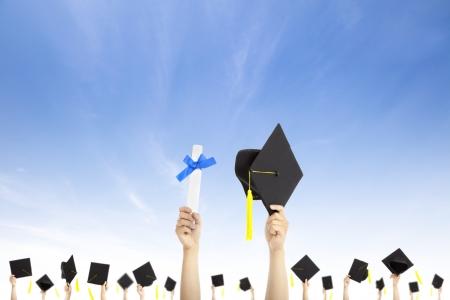 birrete de graduacion: lado la celebración de sombreros de graduación y certificado de título con el fondo de la nube Foto de archivo