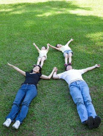 asian family lying on the grass photo