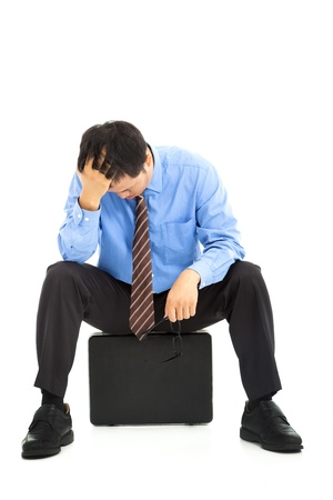 frustrated businessman sitting on the briefcase photo