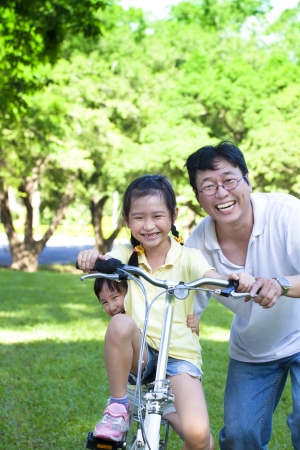 Father with two little girls on the bicycle photo