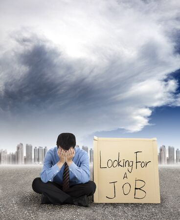 looking for work: businessman looking for a job and city with storm coming