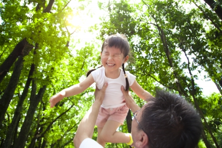 girl bonding: happy little girl with father in the green forest at morning Stock Photo