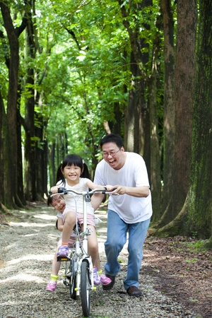 Father Teaching daughter  to riding bicycle photo