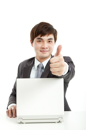 successful businessman working with computer and showing thumb up photo