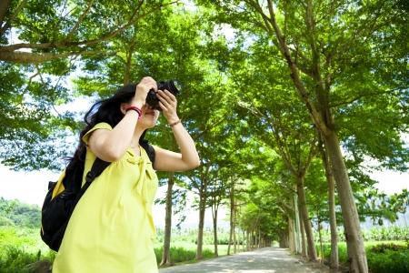 při pohledu na fotoaparát: Mladá žena s batohem stojící na zeleném lese s fotografií Reklamní fotografie