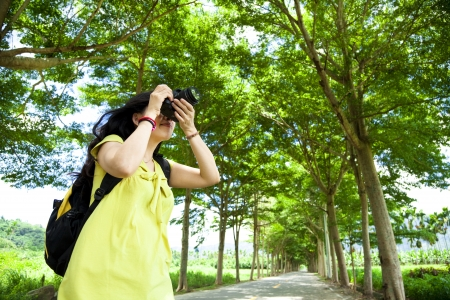 taking photograph: Young woman with backpack standing in the green forest taking photo