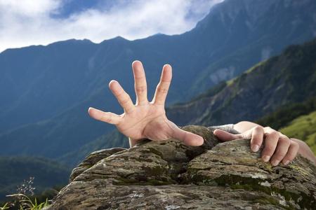 hombre cayendose: la mano en busca de ayuda en la montaña Foto de archivo